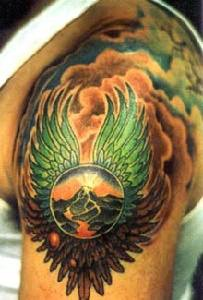 Surreal winged sphere tattoo on shoulder