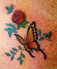 farfalla monarca e rose rosse tatuaggio