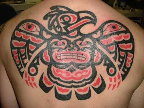 el tatuaje grande de un dios indio en forma de aguila hecho en la espalda en color rojo con negro