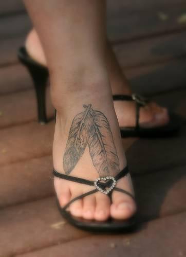 Due piume bianche tatuaggio sul piede