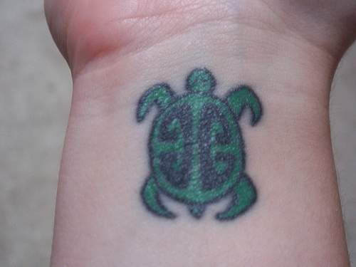 Wrist tattoo with small green turtle