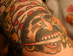 Colored tattoo of pirate with dagger in the mouth