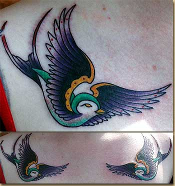 Traditional colored tattoo of two birds on scapulas