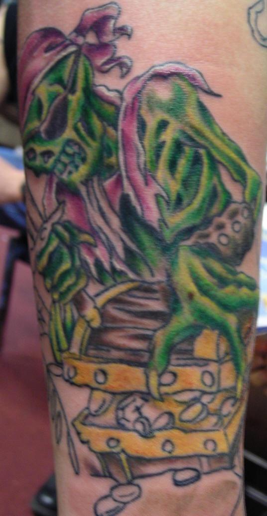 el tatuaje de un esqueleto pirata de color verde con un baul de tesoro