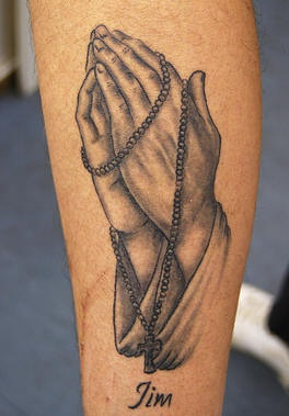 Detailed praying hands and rosary tattoo