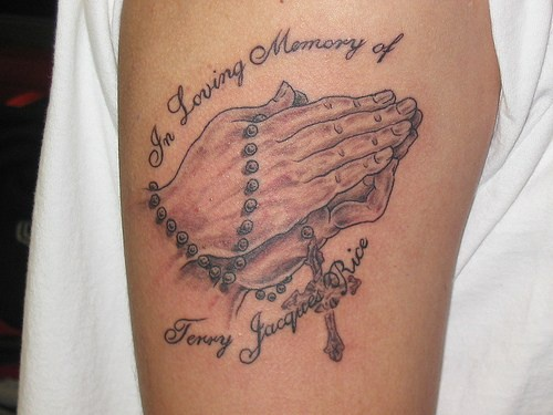 Praying hands with rosary tattoo on arm