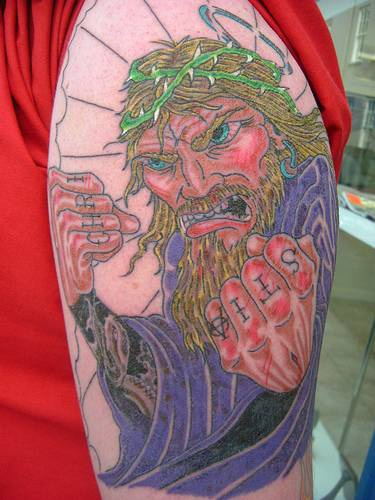 Angry jesus knuckles tattoo on shoulder