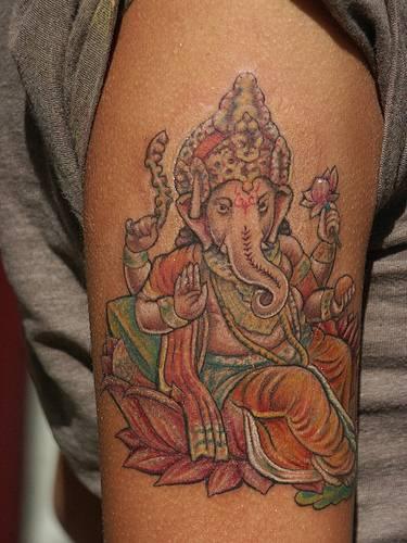 Ganesha on lotus coloured tattoo