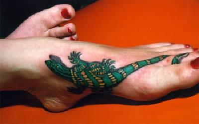 Green and yellow lizard tattoo on foot