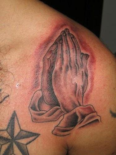 Praying hands tattoo on shoulder