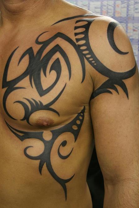 Tatuaggio grande non colorato sul deltoide e sul petto il disegno in stile tribale