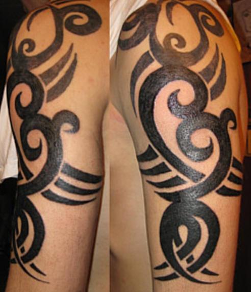 Tatuaggio grande colorato sul deltoide il disegno in stile tribale