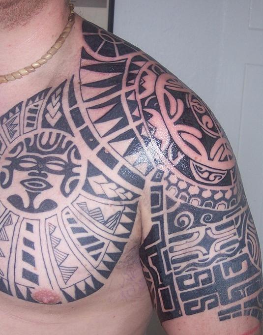 Tatuaggio grande non colorato sul petto e sul deltoide in stile tribale