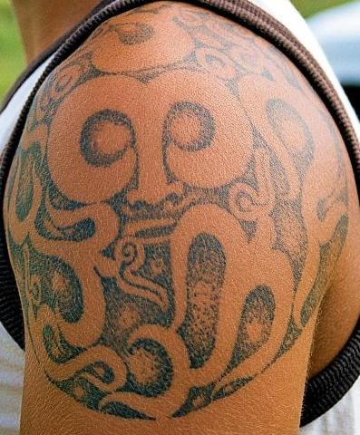 Tatuaggio non colorato sul deltoide in stile tribale