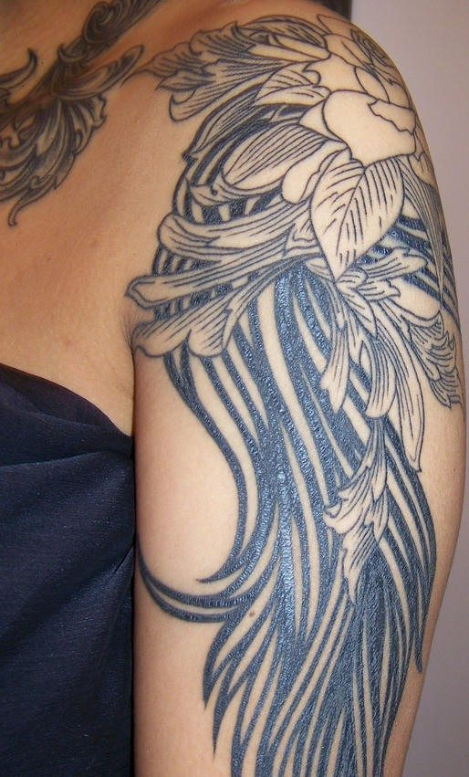 Shoulder tattoo, big black flower, designed with long leaves as tail