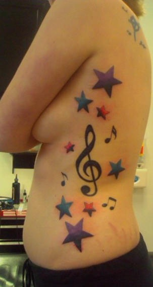 Side tattoo, treble clef with stars and melodies