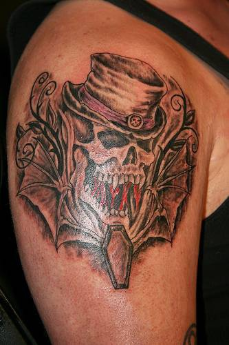 Skull in cylinder with winged coffin tattoo