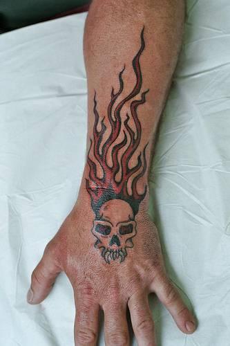 Flaming devil skull tattoo on arm