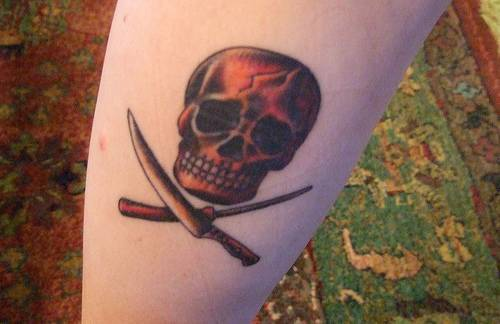 Red skull with crossed tools tattoo