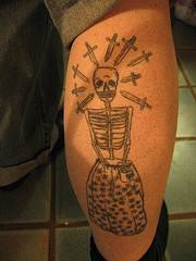 Skeleton in suit with knives tattoo