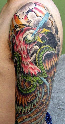 Dragon and bird fight tattoo