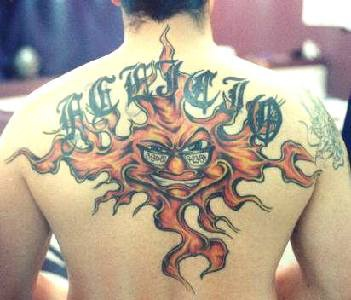 Large sun with writings tattoo on back