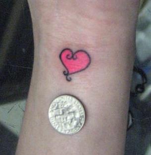 Small pink heart tattoo on wrist