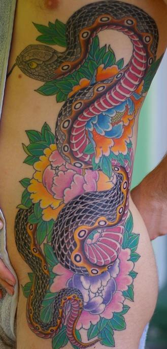 Tatuaggio enorme sul fianco il serpente lungo & i fiori