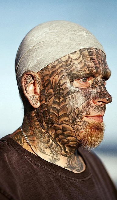 Spider webs tattooed on face