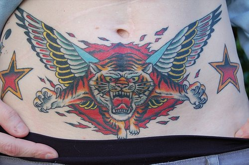 Stomach tattoo, angry, winged tiger flying from fire