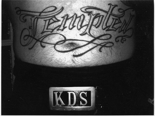 Stomach tattoo, tempted, curled styled  inscription