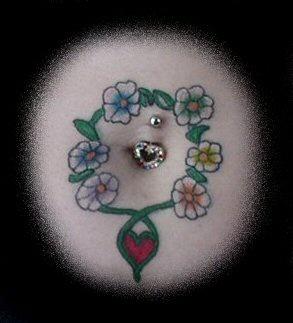 Tatuaggio piccolo sulla pancia i fiori e il cuore attorno del ombelico