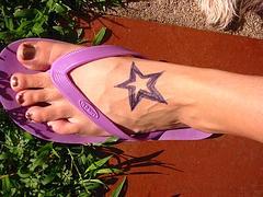 Purple star tattoo on foot