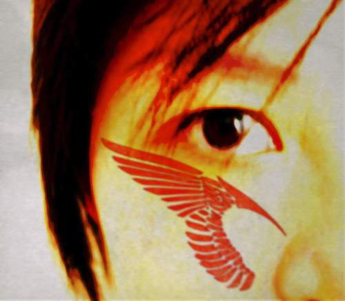 Red tattoo of angel wing on cheek