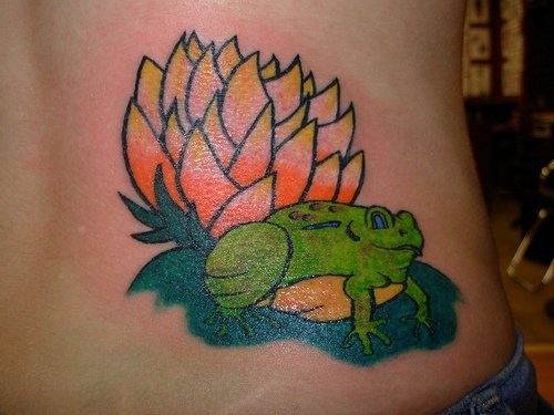 Green frog on upper back tattoo with lily