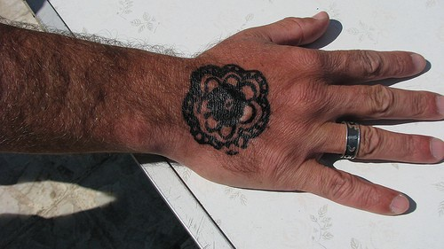 Black flower in chain ,styled  tattoo on hand