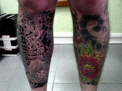 Tatuaggio colorato sulle gambe in stile floristico