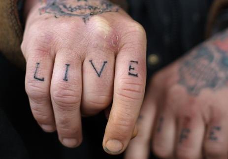 """Tatuaggio sulle dita la scritta """" live life"""""""