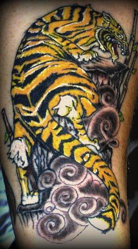 Asian tiger crawling on rocks tattoo