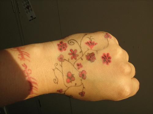 Tree hand tattoo with red flowers