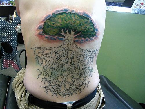 Back tattoo of tree with green leaves and big root