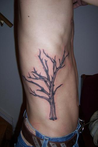 Side tattoo of lonely withered tree