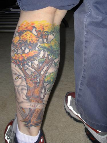 Leg tattoo with female colored tree