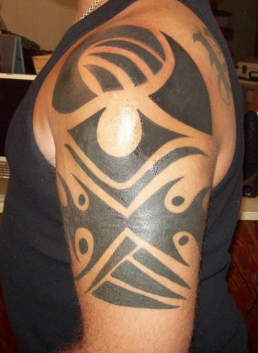 Black tribal shoulder tattoo with eye