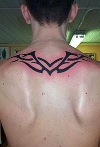 Black wings tribal tattoo on upper back