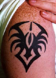 Shoulder tattoo with small tribal spider