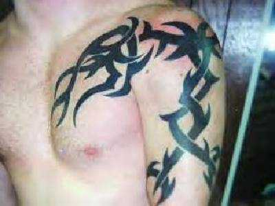 Black tribal tattoo on chest and shoulder