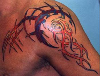 Colored tribal tattoo on chest and shoulder