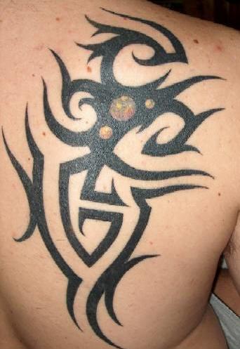 Black tribal sign tattoo on scapula