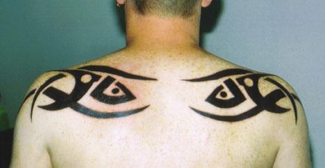 Tattoo of tribal eyes on upper back